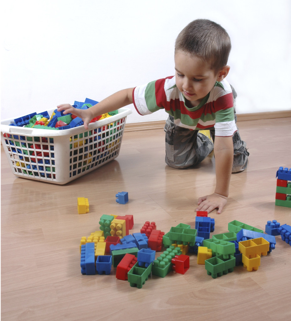 Мальчик собирает игрушки - фото